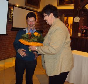 Frau Radtke übergibt Frau Michaelis Blumen